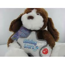 Shining star dog, Floppy ears, brown eyes and fur, holding a big star - Shining Star Dog. It holds a star with the Shining Star name on it, No tag attached. It is has brown and white fur and plays music. It has brown eyes.
