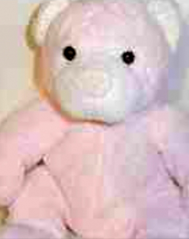 Worn out grayish-pinkish bear with a pink nose and a label that says
