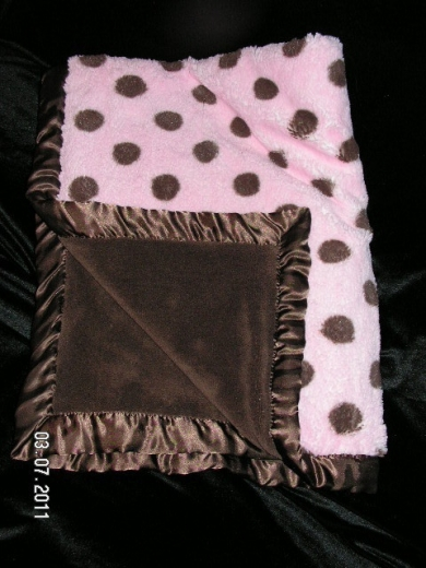 Chocolate brown blanket with brown satin edges and pink polka dots on one side