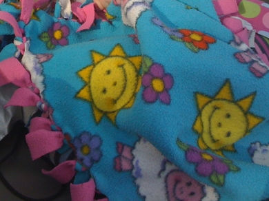 Teal and pink fleece tie blanket with sheep, flower, and sun print