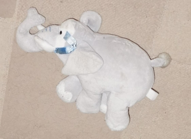 Light grey elephant with blue bow on left ear and makes sound when foot pressed