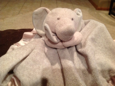 Light pink elephant (head and arms) attached to a gray and white  binkie blanket.