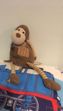 Monkey with stripes on arms and legs. Brown in colour and well loved.