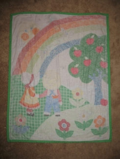 Baby blanket with picture on one side, white with flowers on the other, and green trim, lost at go