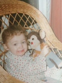 brown teddy monkey with white face, yellow/orange v-neck jumper and blue and white stripped pants