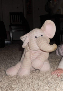 Pink and white striped elephant. Curved nose.  Floppy ears. Bean bag type feet to weigh them down