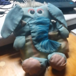 blue elephant with floppy ears with a tan bottom is striped. has little white tusks