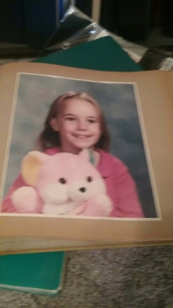 Pink bear with one yellow ear and one blue ear and there is a picture on the tummy