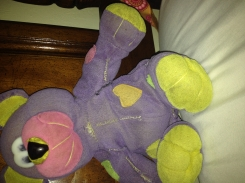 Purple teddy with rainbow patches and yellow feet.