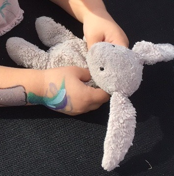 Pinkish grey worn jellycat bunny with holes in hand, chest and foot