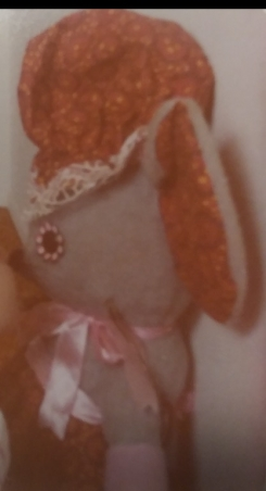 Gray mouse with red hat and pink ribbon around neck