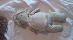 Soft plush baby doll with stitched face and pink hat