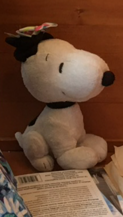 A black and white smiling snoopy, sitting down,