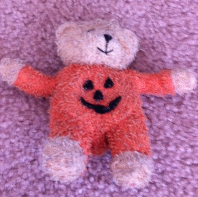 Hand-sized, plush bear in pumpkin suit