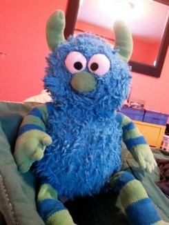 Blue Monster with green horns, nose, and hands.