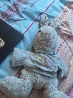 Plush bunny wearing shirt with a yellow flower and a pink flower