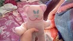 Pink cat with white stripes, blue eyes, blue nose, pink smile, and whiskers