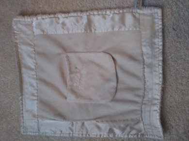 White tiny blanket with bunny pocket on front