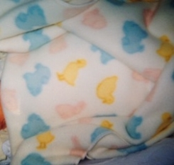 White fleece blanket with yellow ducks, pink rabbits, and blue lambs.